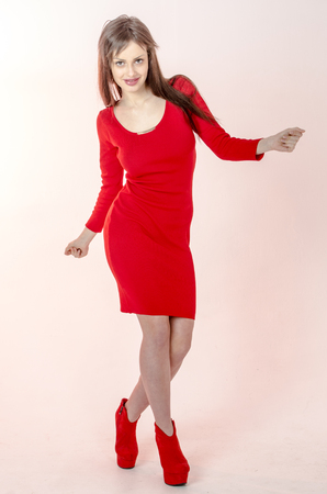 Young go go girl with a beautiful figure in a trendy red dress in skin-tight miniskirt and red high heels and platform dressed for a party and bag with sunglasses