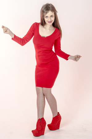 Young girl with a beautiful figure in a trendy red dress in skin-tight miniskirt and red high heels and platform dressed for a party with a disco ball