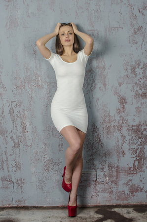 Young girl with a beautiful figure in a trendy white dress in skin-tight miniskirt and red high heels and platform dressed for a party