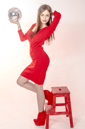 Young girl with a beautiful figure in a trendy red dress in skin-tight miniskirt and red high heels and platform dressed for a party Stock Photo