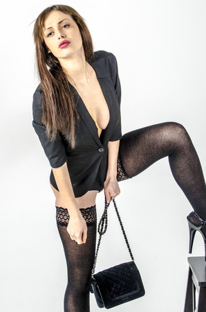 Young go go girl with a beautiful figure in a trendy black dress in skin-tight miniskirt and black high heels and platform dressed for a party and bag with sunglasses