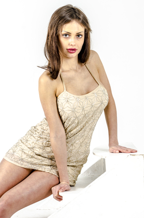 Young go go girl with a beautiful figure in a trendy golden dress in skin-tight jacket and black high heels and platform dressed for a party Stock Photo