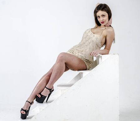 Y Young go go girl with a beautiful figure in a trendy golden dress in skin-tight jacket and black high heels and platform dressed for a party
