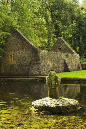 croce celtica: Vecchia croce celtica (5 � secolo) con la cappella in rovina sfondo a St Patrick's Well in Irlanda.