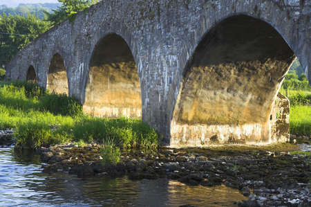 atmospheric: Ancient bridge in Ireland bathed in the sunset light.