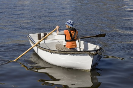 Young man rowing a boat on the river. photo