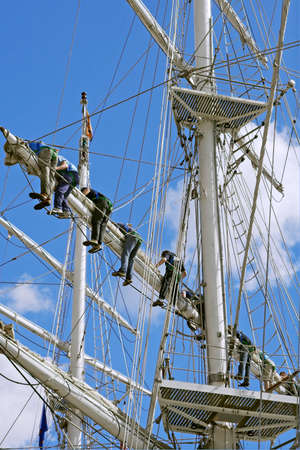 foretop: Crew of the tall ship lowering sails. Stock Photo