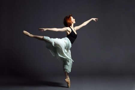 Ballet dancer dancing on grey background. Stock Photo