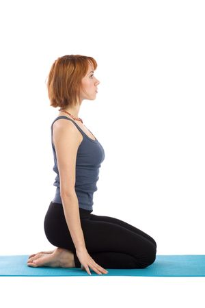 Fit, young woman sitting on mat, isolated over white background.