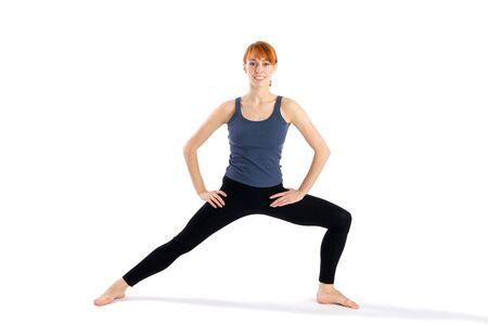 parsvakonasana: Woman in opening pose for yoga exercises called Virabhadrasana and Parsvakonasana, isolated on white background