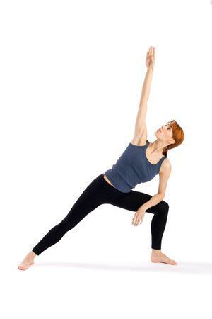 parsvakonasana: Woman doing Yoga exercise called Parsvakonasana (Extended Side Angle Pose - Parsvakonasana), isolated on white background. Stock Photo