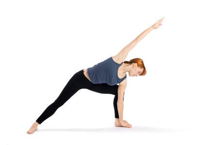 parsvakonasana: Woman doing yoga exercise called Parsvakonasana, isolated on white background.