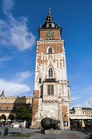 housed: Town Hall gothic tower in Main Market Square in the Old Town district of Cracow, Poland. Built of stone and brick at the end of the 13th century, Its cellars once housed a city prison with a medieval torture chamber. Stock Photo