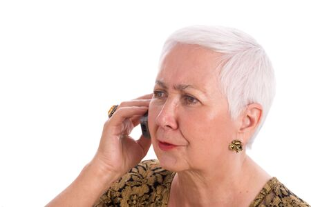 phone isolated: Worried senior woman talking on the phone, isolated on white background. Stock Photo