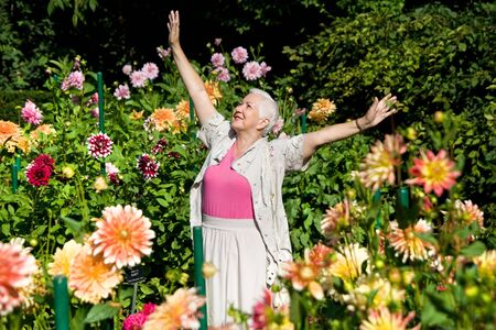 Happy senior woman expressing positivity in the garden full of flowers.