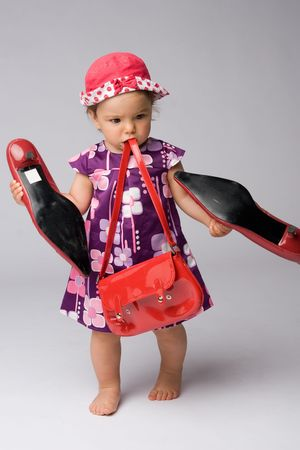 Funny shot of one year old fashion girl with red purse and big adult shoes. Stock Photo