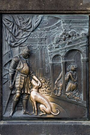 return trip: An old relief below the statue of St. John of Nepomuk on Charles Bridge in Prague, Czech Republic. According to legend good luck and a promise of return trip to Prague comes to those who touch it.