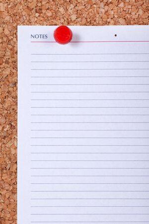 annoucement: Blank note paper on corkboard macro closeup.