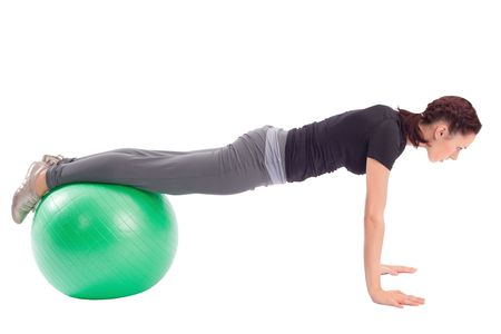 Young woman with gym ball doing pushup exercise, isolated on white background. Stock Photo - 6310759