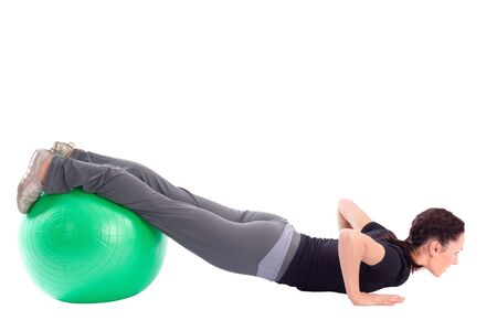 Young woman with gym ball doing pushup exercise, isolated on white background. photo