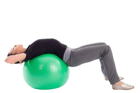 Young woman with gym ball doing situps exercise, isolated on white background. photo
