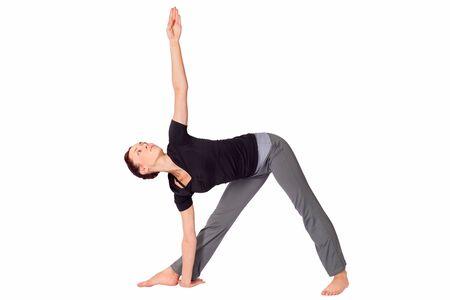 trikonasana: Young fit woman doing yoga exercise called Triangle Pose (Sanskrit name: Trikonasana), isolated on white background. Stock Photo