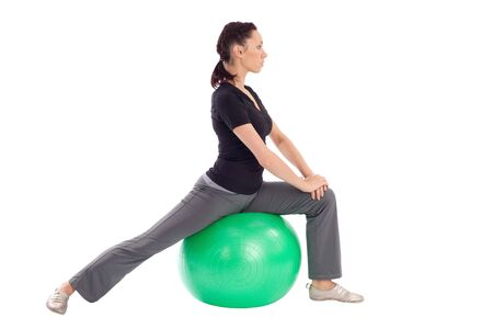 Young slim woman with gym ball doing stretching exercise, isolated on white background. photo