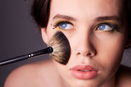 Beauty shoot of a young woman with long eyelashes blue eyes and makeup brush touching her face. Shallow depth of field. Stock Photo
