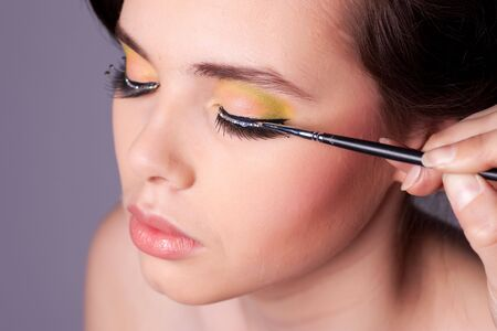 Applying professional makeup on young woman face. Shallow depth of field. photo