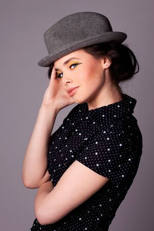 Fashion shoot of an attractive young woman wearing dark blouse and a hat. photo