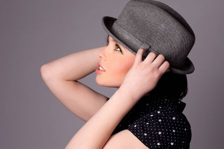 Beautiful stylish young woman with full makeup posing with a hat. photo