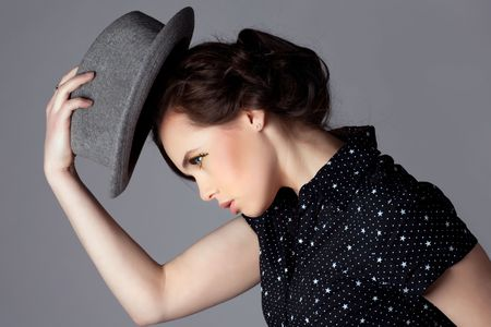 Young woman take off her hat and bow, side view. photo
