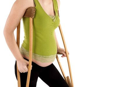 9 months: Nine month pregnant woman  with crutches close-up, isolated on white background