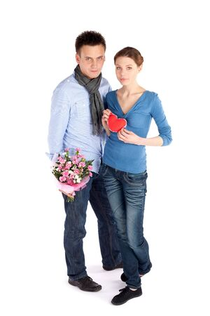 Young attractive couple in love. Woman holding red heart, man holding flowers, isolated on white background. Stock Photo - 6735264