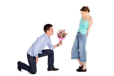 inginocchiarsi: Felice bel giovane uomo consegna un fiori per una bella giovane donna isolata on white