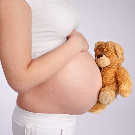Pregnant mother showing her belly and holding a teddy bear photo