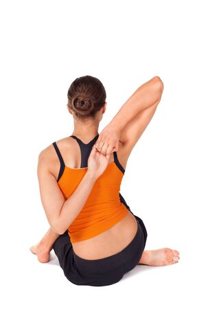 sanskrit: Woman doing yoga exercise called Cow Face Pose, sanskrit name: Gomukhasana, pose useful in arthritis and dry piles, removes pain in hip and lower extremities, isolated on white Stock Photo