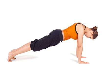 pushup: Fit slim woman doing yoga exercise called Plank Pose, sanskrit name: Kumbhakasana, pose strengthen wrists, arms, shoulders, back, legs, and abdomen, lengthens the spine, isolated on white Stock Photo