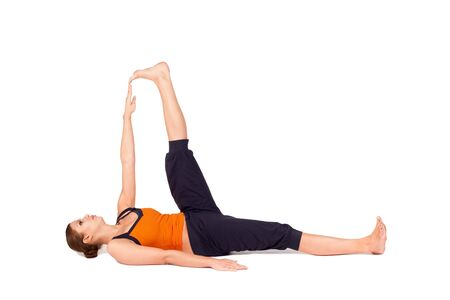 hamstring: Woman doing Reclining Big Toe yoga pose (there are four versions of this exercise), sanskrit name: Supta Padangusthasana, this pose stretches the hips, groins, thighs, hamstrings, calves, relieves backache, sciatica, and menstrual discomfort