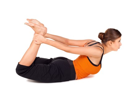 enhancing: Woman practicing yoga exercise called Bow Pose sanskrit name: Dhanurasana, this pose improves posture, rejuvenates the spine, enhancing blood circulation, stretches ankles, thighs and groins, abdomen, chest, throat, and deep hip flexors, strengthens back