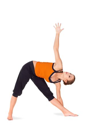 strengthen: Fit attractive young woman practicing yoga exercise called Triangle Pose, sanskrit name: Trikonasana, this pose strengthen thighs, calves, ankles and back, improves strength, stability and balance Stock Photo