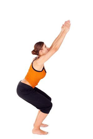 sanskrit: Woman practicing yoga exercise called: Chair Pose, sanskrit name: Utkatasana, this pose increases strength, balance and stability, isolated on white