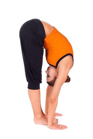 sanskrit: Woman practicing yoga exercise called Standing Forward Bend, sanskrit name: Uttanasana, this posture stretches the back of the legs, hips, spine, good as a back pain relief