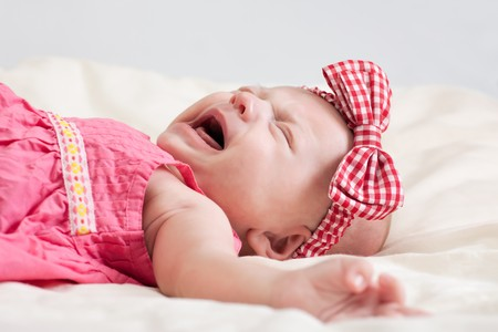 fussy: Crying ten weeks old baby girl on bed Stock Photo