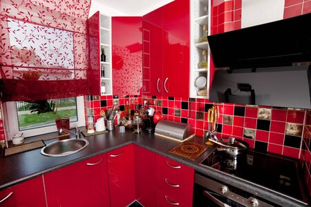 Close up shoot of a red modern kitchen including kitchenware photo