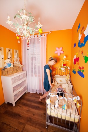 drawing room: Wide shoot of a mother and child in a well designed small but comfortable baby room Stock Photo