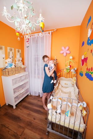 Wide shoot of a mother and child in a well designed small but comfortable baby room Stock Photo