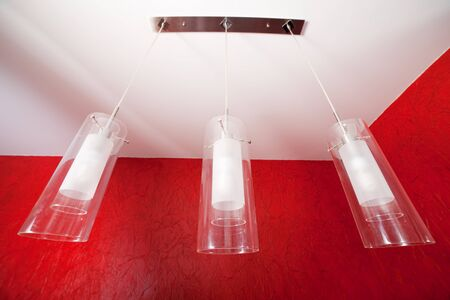 Abstract ultra-wide view on a three modern ceiling lights in a living room with red wallpaper photo