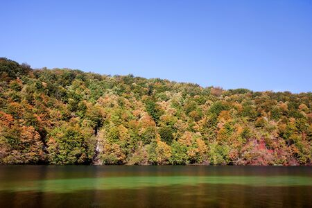 Landscape with early autumn forest on a hill, lake and blue sky photo