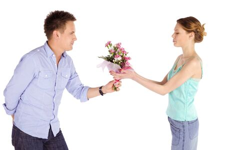 Casual couple isolated on white, a man giving flowers to his girlfriend